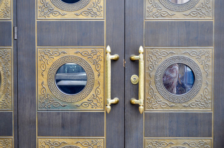 Photo pour Texture of old decorative beautiful wooden door gates with patterned ornaments and gold ornaments, elements and gold door handles. The background. - image libre de droit