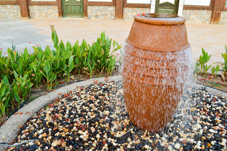 Photo pour A beautiful little fountain in the form of a brown vase, a jug with falling drops of water on colored stones standing in a flower bed with green plants. - image libre de droit