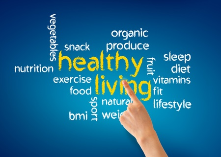 Photo pour Hand pointing at a Healthy Living illustration on blue background. - image libre de droit