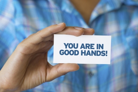 Photo for A person holding a white card with the words You are in Good hands - Royalty Free Image