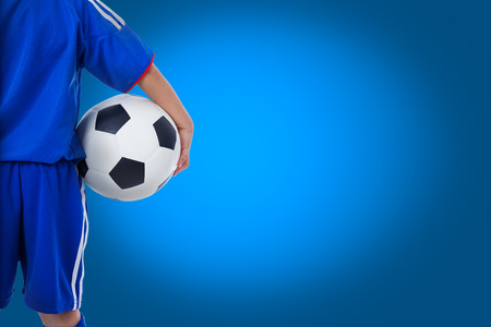 Back view of youth soccer player in blue uniform and little kid holding a ball. Some space for input text message on blue background