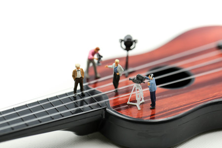Photo for Miniature people : Director, staff and actors on the set of the video singer  with  guitar,production music concept. - Royalty Free Image
