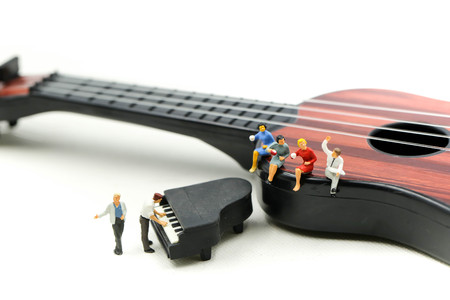 Photo pour Miniature people : man play mini piano with  sitting on acoustic guitar. time of relax or music relax concept. - image libre de droit