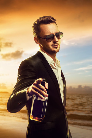 Photo pour Attractive disheveled young man wearing elegant black suit and sunglasses holding a bottle of whiskey and pointing ahead after party on sunset beach background - image libre de droit