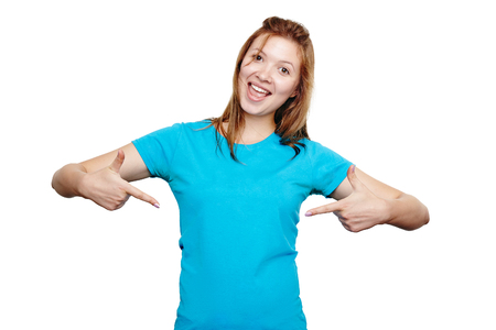 Foto de t-shirt design concept. Excited happy young woman pointing to empty space on her blue t-shirt with both hands, isolated on white - Imagen libre de derechos