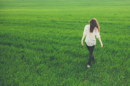 Foto de Unrecognizable lonely sad girl walking on summer meadow. Rear view. Sadness and loneliness concept with copy space. - Imagen libre de derechos