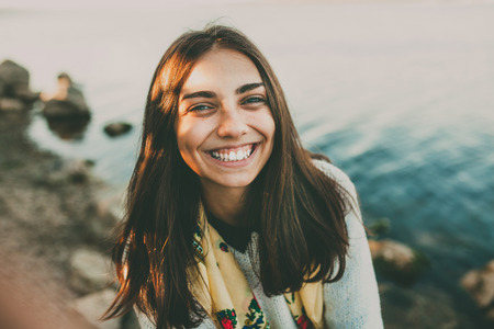 Photo pour Happy teenage girl standing outdoors on autumn day by a lake. Smiling adorable girl outside. - image libre de droit