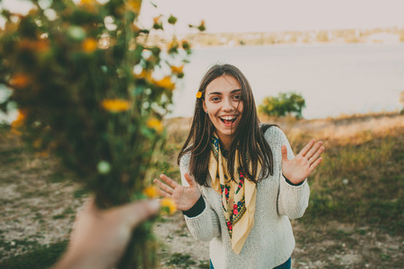 Foto per Surprise for your girlfriend..Giving flowers gift. Excited teen girl. - Immagine Royalty Free