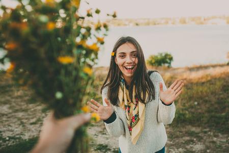 Foto de Surprise for your girlfriend..Giving flowers gift. Excited teen girl. - Imagen libre de derechos