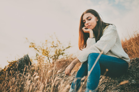 Foto de Teenage girl sitting alone on autumn cold day. Lonely sad young woman wearing warm sweater thinking and hesitating. Loneliness and solitude concept. - Imagen libre de derechos