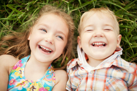 Foto de Top view portrait of two happy smiling kids lying on green grass. Cheerful brother and sister laughing together. - Imagen libre de derechos