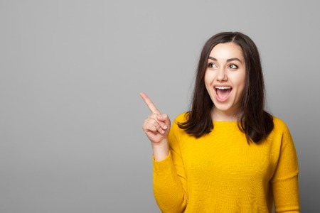 Photo pour Excited young woman pointing her finger towards blank space isolated over grey background - image libre de droit