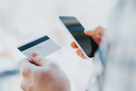 Photo pour Closeup young man hands holding credit card and using cell, smart phone for online shopping or reporting lost card, fraudulent transaction - image libre de droit