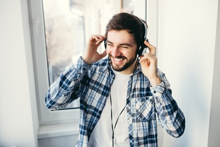 Photo for Portrait of a young handsome man with headphones smiling and listening to music - Royalty Free Image