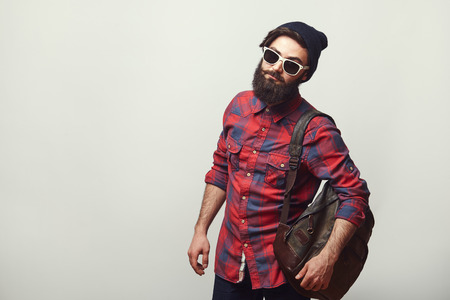 Photo for Fashion portrait of bearded hipster young man wearing sunglasses, backpack and hat over grey background with copyspace. Confident man with beard. - Royalty Free Image
