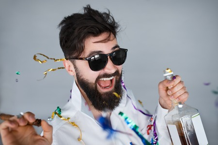Photo pour Bearded man with sunglasses holding a bottle of alcohol and cigar at celebration. Ecstatic portrait of drunk man having fun at wild party - image libre de droit