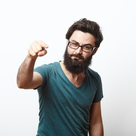 Foto de portrait of a angry young man with beard and glasses wearing t-shirt pointing to camera. We need you concept - Imagen libre de derechos