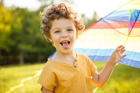Photo pour Young boy putting out tongue holding kite - image libre de droit