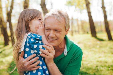 Foto de Little girl telling secret to grandpa - Imagen libre de derechos