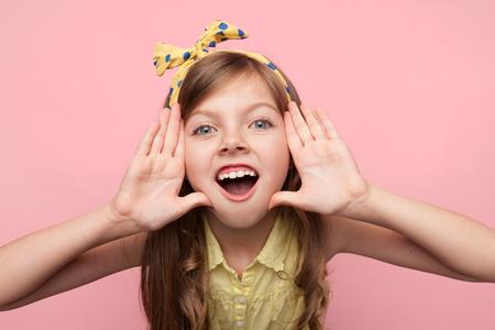 Photo pour Little girl shouting at camera on pink - image libre de droit