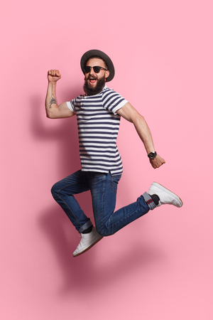 Photo for Stylish man jumping on pink - Royalty Free Image
