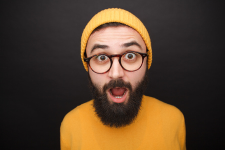 Photo pour Amazed bearded man in yellow hat - image libre de droit