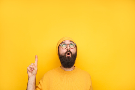 Photo pour Interested hipster pointing up on yellow - image libre de droit