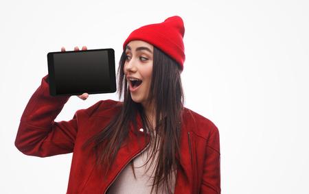 Foto de Bright brunette demonstrating modern tablet - Imagen libre de derechos