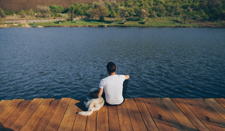 Photo pour Anonymous man with dog sitting on pier - image libre de droit