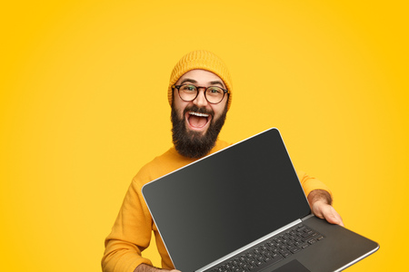 Photo pour Smiling man promoting modern laptop - image libre de droit