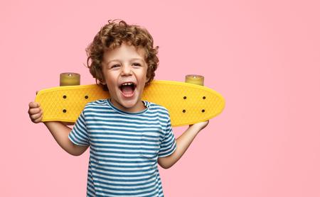Foto per Cute boy with yellow skateboard - Immagine Royalty Free