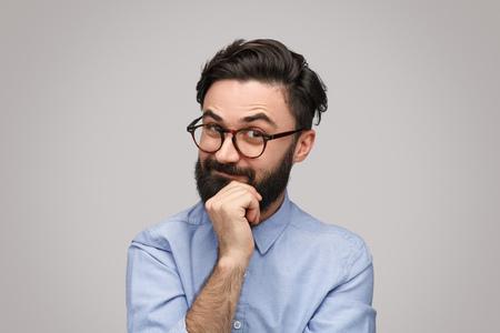 Photo pour Thoughtful guy rubbing chin - image libre de droit