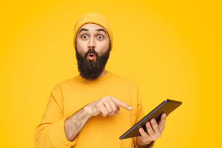 Foto de Surprised man pointing at tablet - Imagen libre de derechos