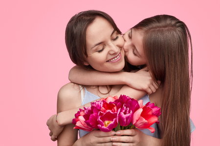 Photo pour Girl kissing mother with spring bouquet - image libre de droit