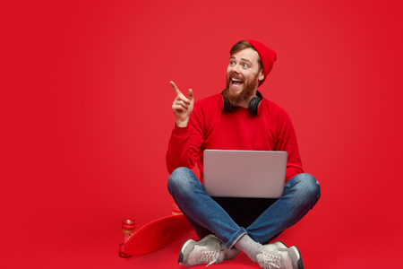 Foto de Excited hipster with laptop pointing aside - Imagen libre de derechos