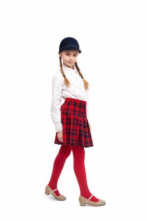 Foto de Schoolgirl in stylish hat looking at camera - Imagen libre de derechos