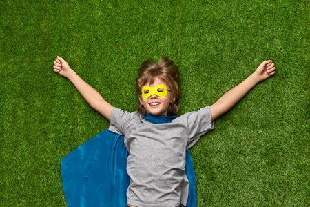 Foto de Cheerful superhero relaxing on grass - Imagen libre de derechos