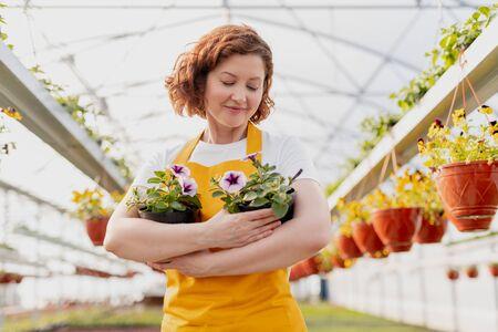 Photo pour Female gardener embracing potted flowers - image libre de droit
