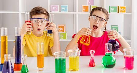 Foto de Rapturous mates making experiment with bright liquid at school - Imagen libre de derechos