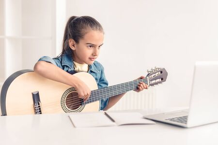 Foto de Little girl learning to play guitar online - Imagen libre de derechos