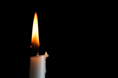 A single white candle burns shining into the darkness with nice text space