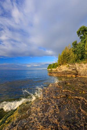 Gentle waves splash on the rocky shoreline of Door County, Wisconsin