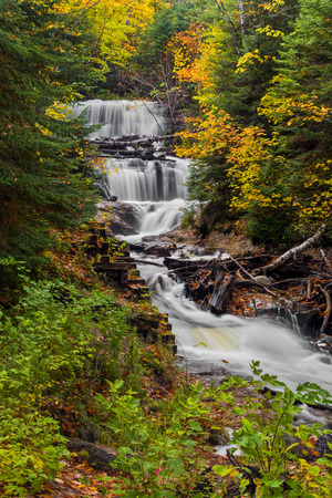 Sable Falls, a waterfall in Upper Peninsula Michigan\'s Pictured Rocks National Lakeshore, is surrounded by fall color and evergreen trees.