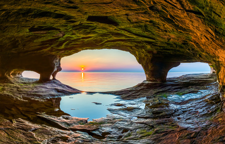 Foto de The setting sun, reflected upon the chilly waters of Lake Superior, is viewed from a sea cave along the Upper Peninsula coast of northern Michigan. - Imagen libre de derechos