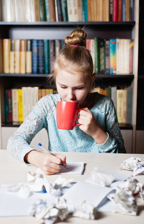 Beautiful young girl sitting on workplace with crumpling the sheet and drinking tea