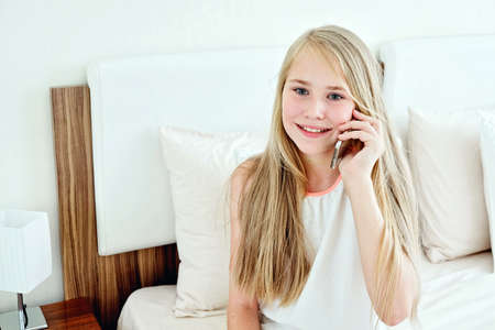 Foto de Teenage Girl Lying On Bed Using A Mobile Phone - Imagen libre de derechos