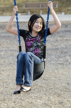 young Asian girl wedged in a kiddie swing