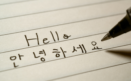 Photo pour Beginner Korean language learner writing Hello word Annyeonghaseyo in Korean characters on a notebook close-up shot - image libre de droit