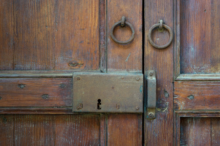 Photo pour Closeup of a wooden aged latch and two rusted ring door knockers over an ornate wooden door, Cairo, Egypt - image libre de droit