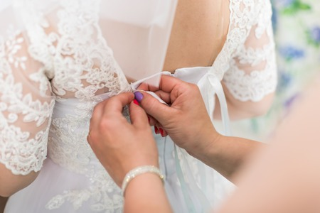 Photo for Hands of girlfriend helping the bride to dress her dress and tie a corset - Royalty Free Image